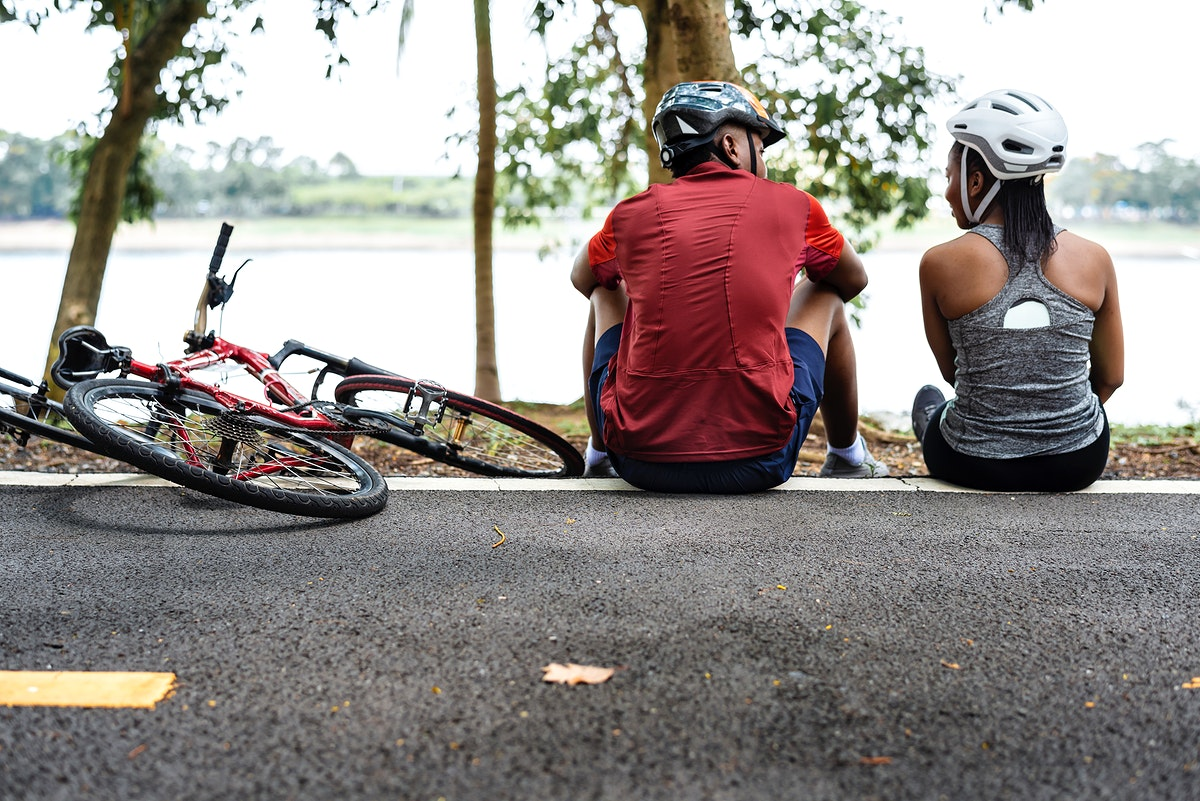 Cyclist couple resting in a park