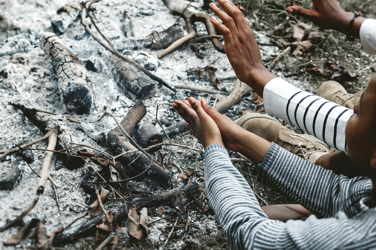 Warming hands by the campfire ashes