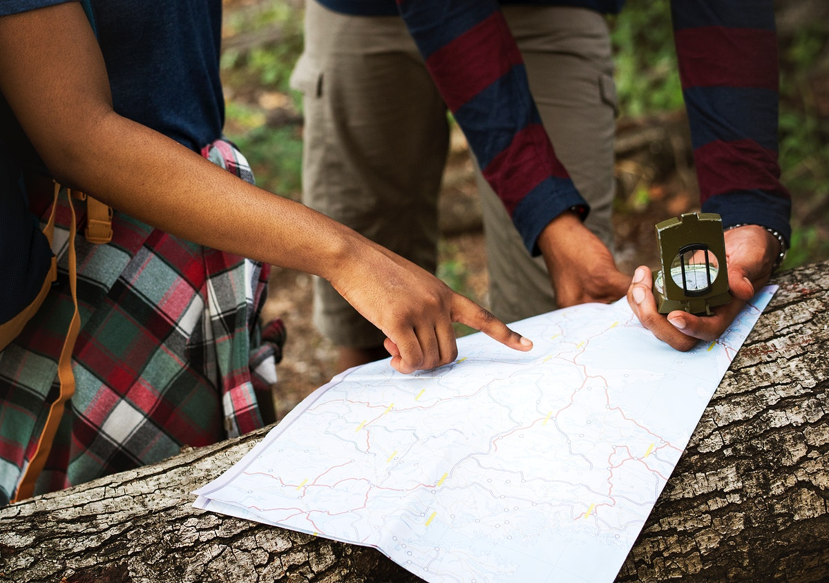 Trekking couple using map and compass in a forest