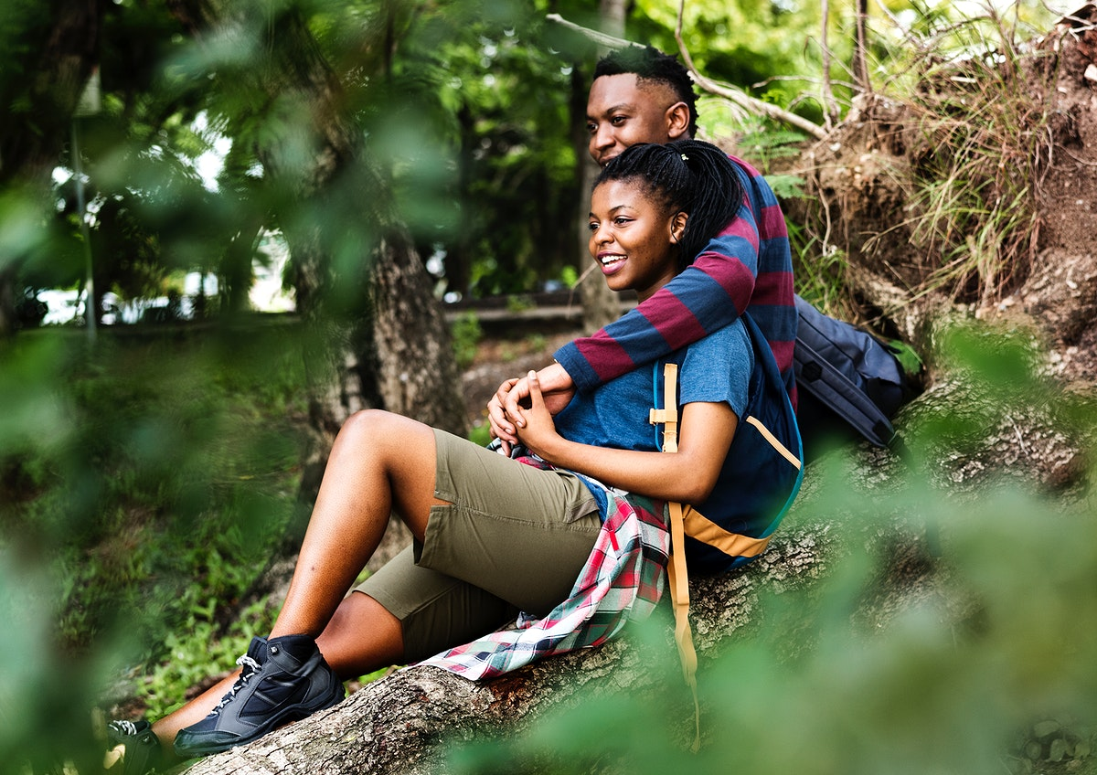 Trekking couple resting on a tree trunk