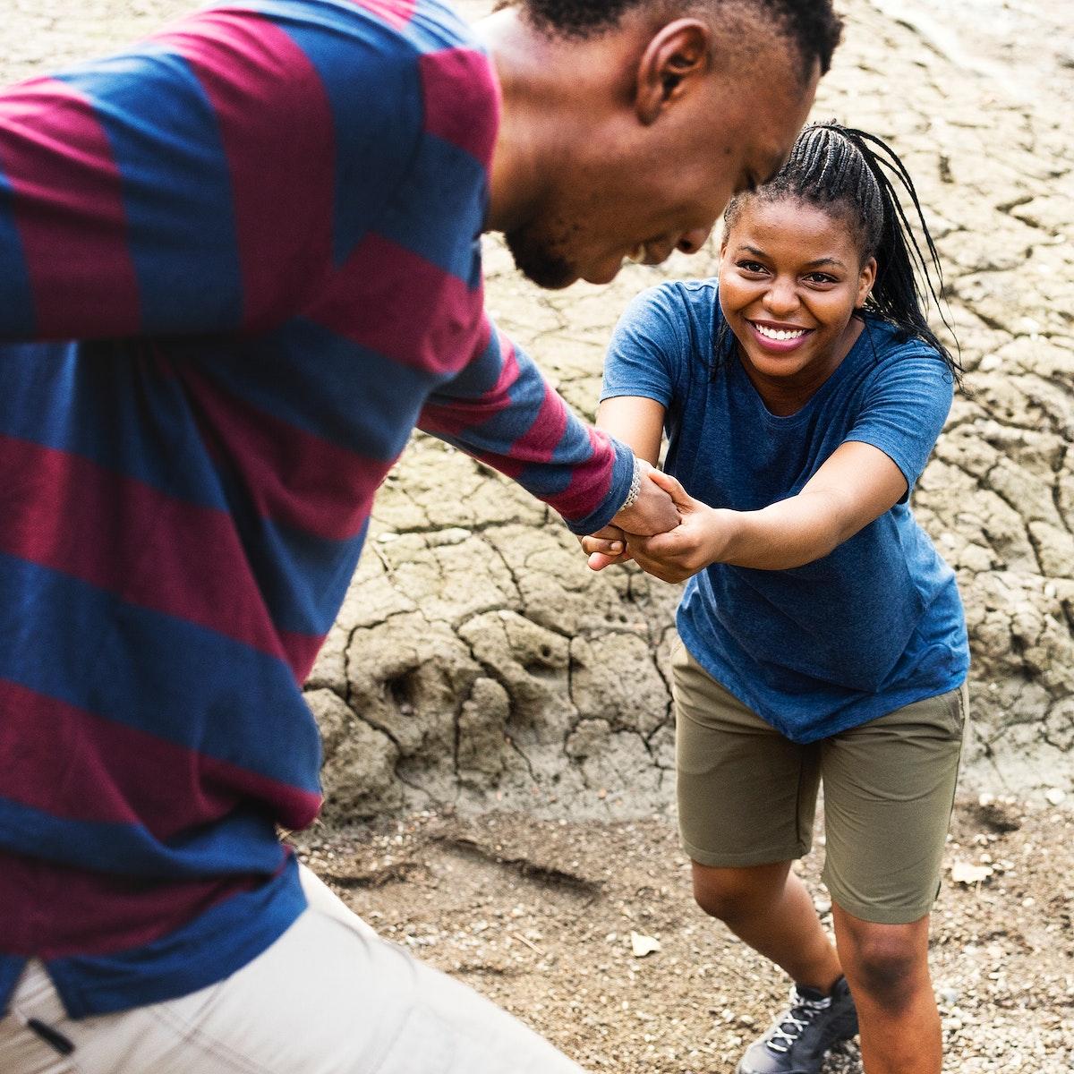 Man helping his girlfriend on a trek
