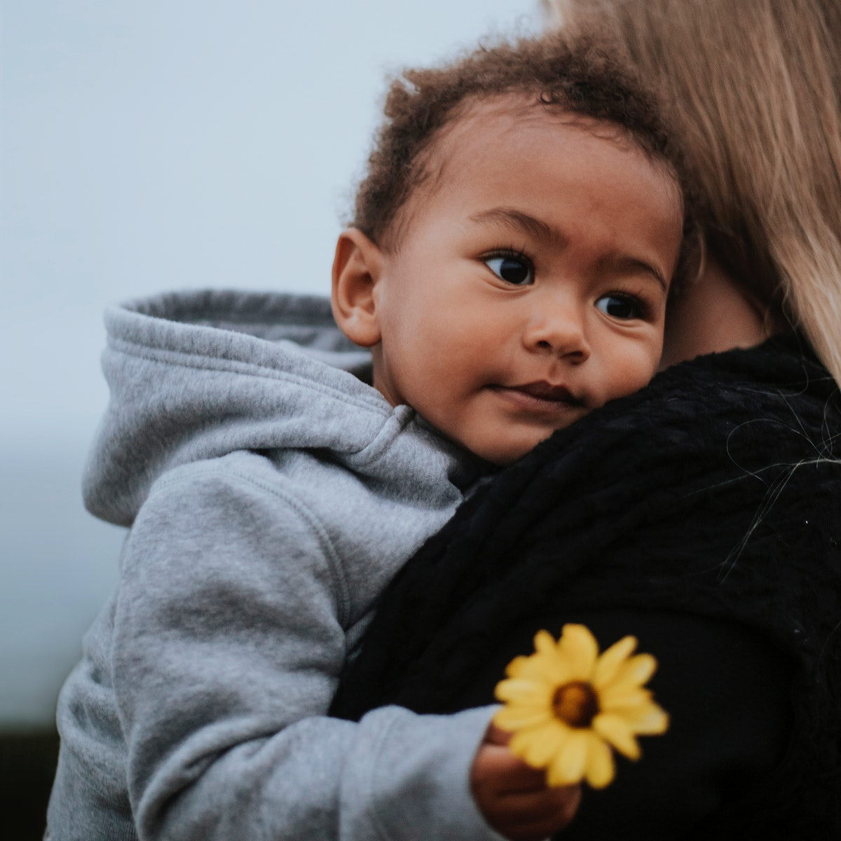 Young boy holding a flower while being carried by his mom