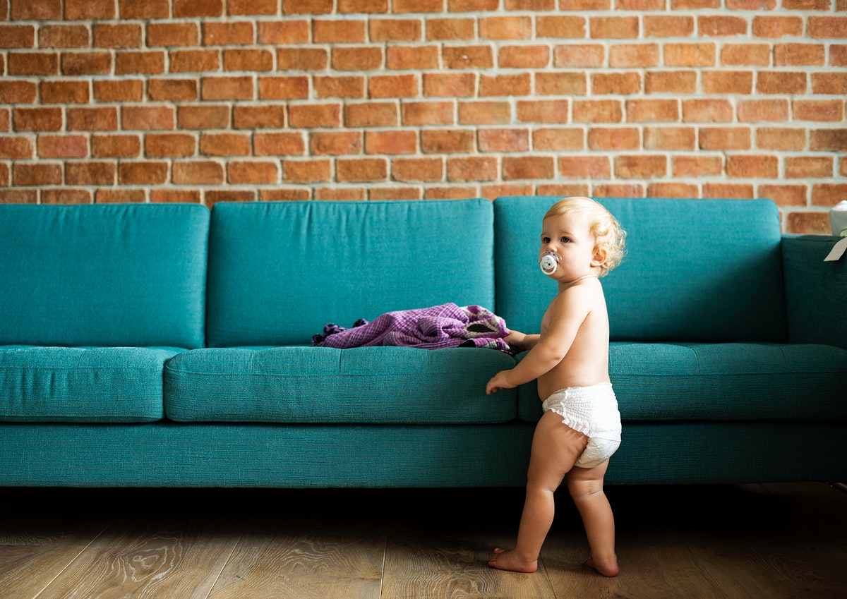 Baby standing by the couch
