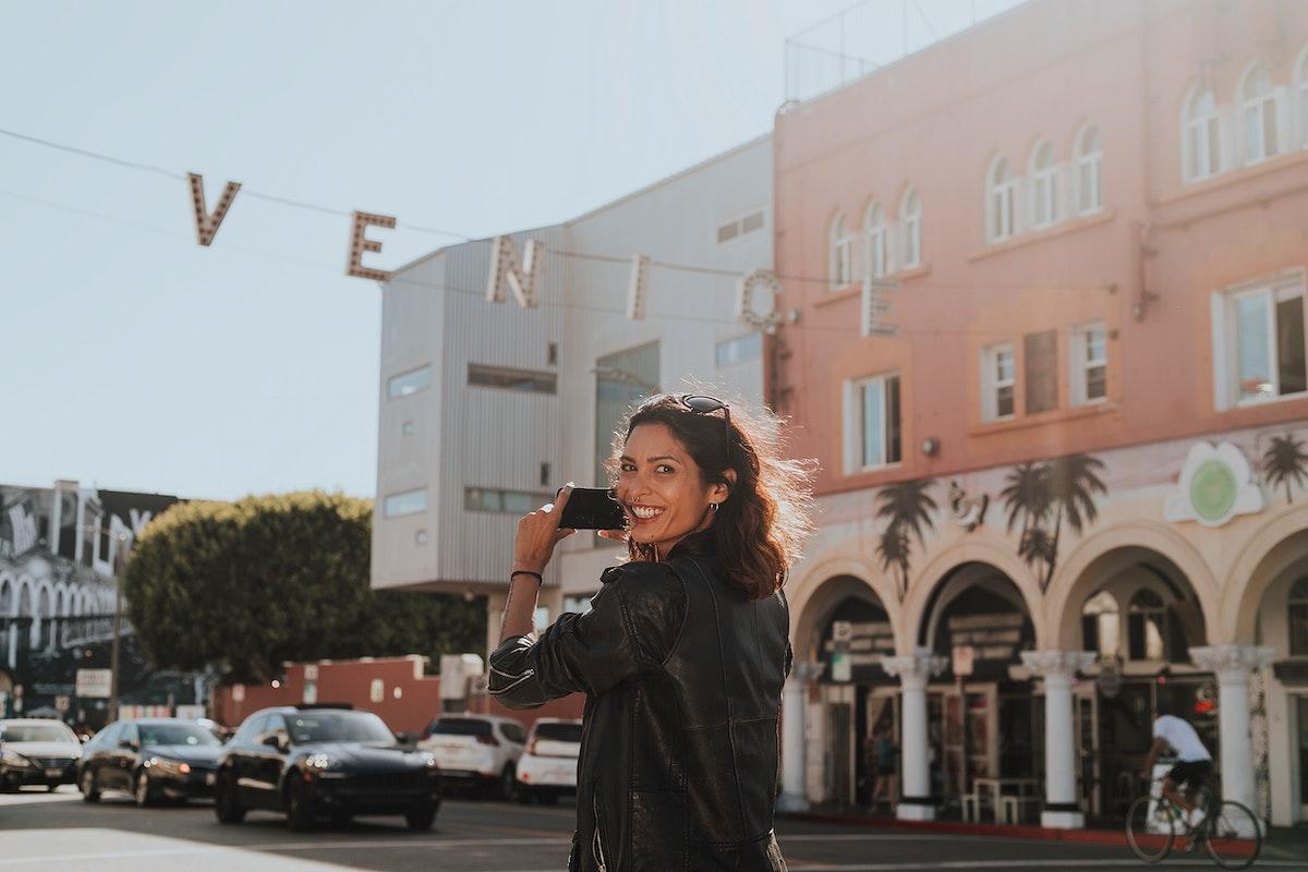 Cheerful woman taking a photo of Venice Beach