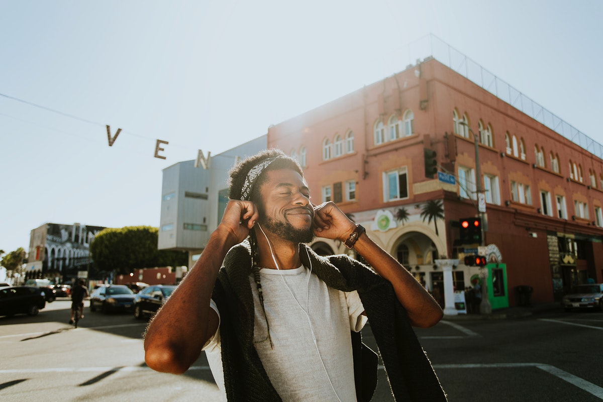 Young man enjoying music while walking in the streets