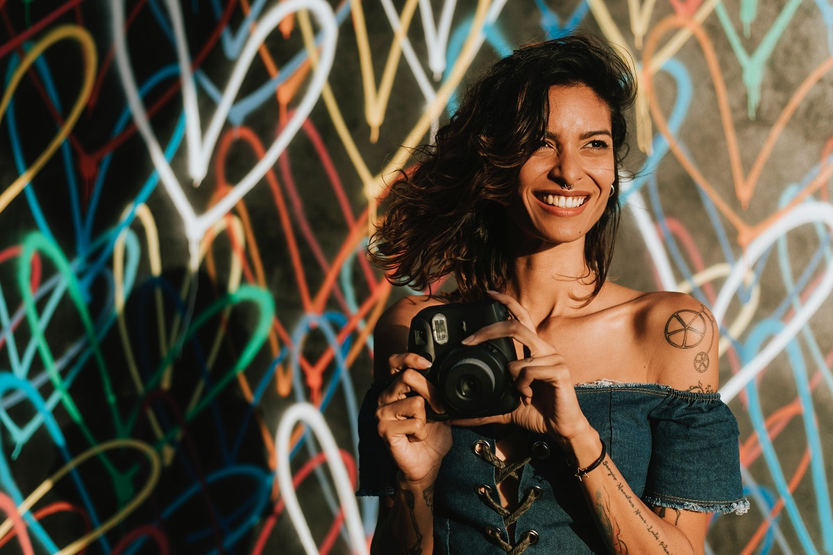 Cheerful woman using an instant camera against the backdrop featuring the graffiti artwork by James Goldcrown in Los Angeles…