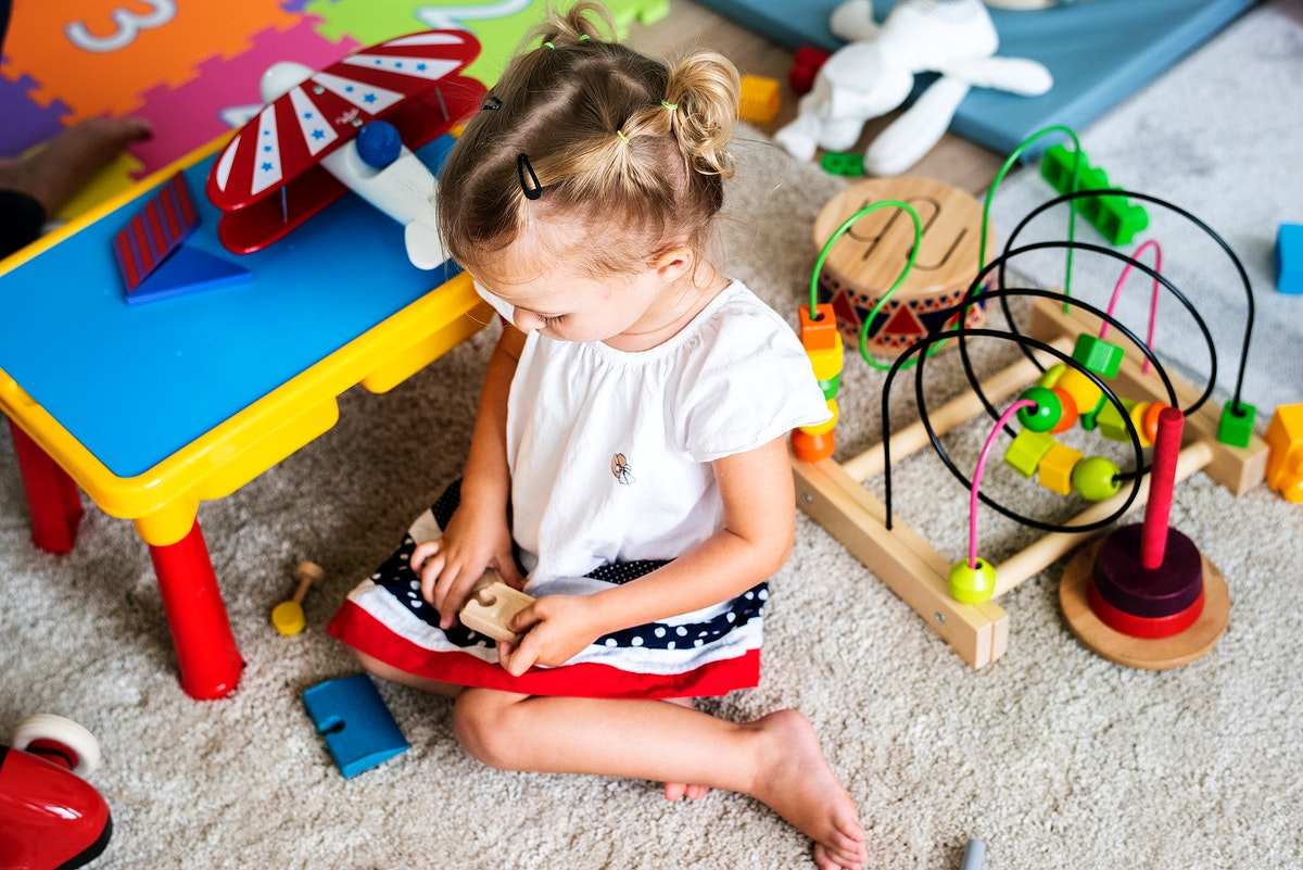 Little girl playing toys in the playroom