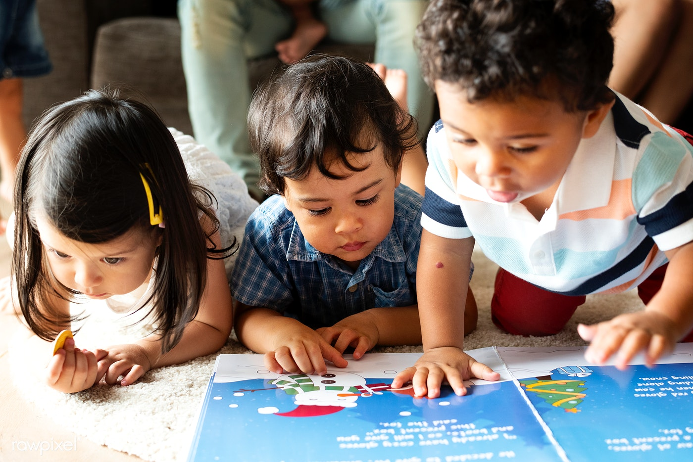 Image by Rawpixel of preschool children looking at a story book.