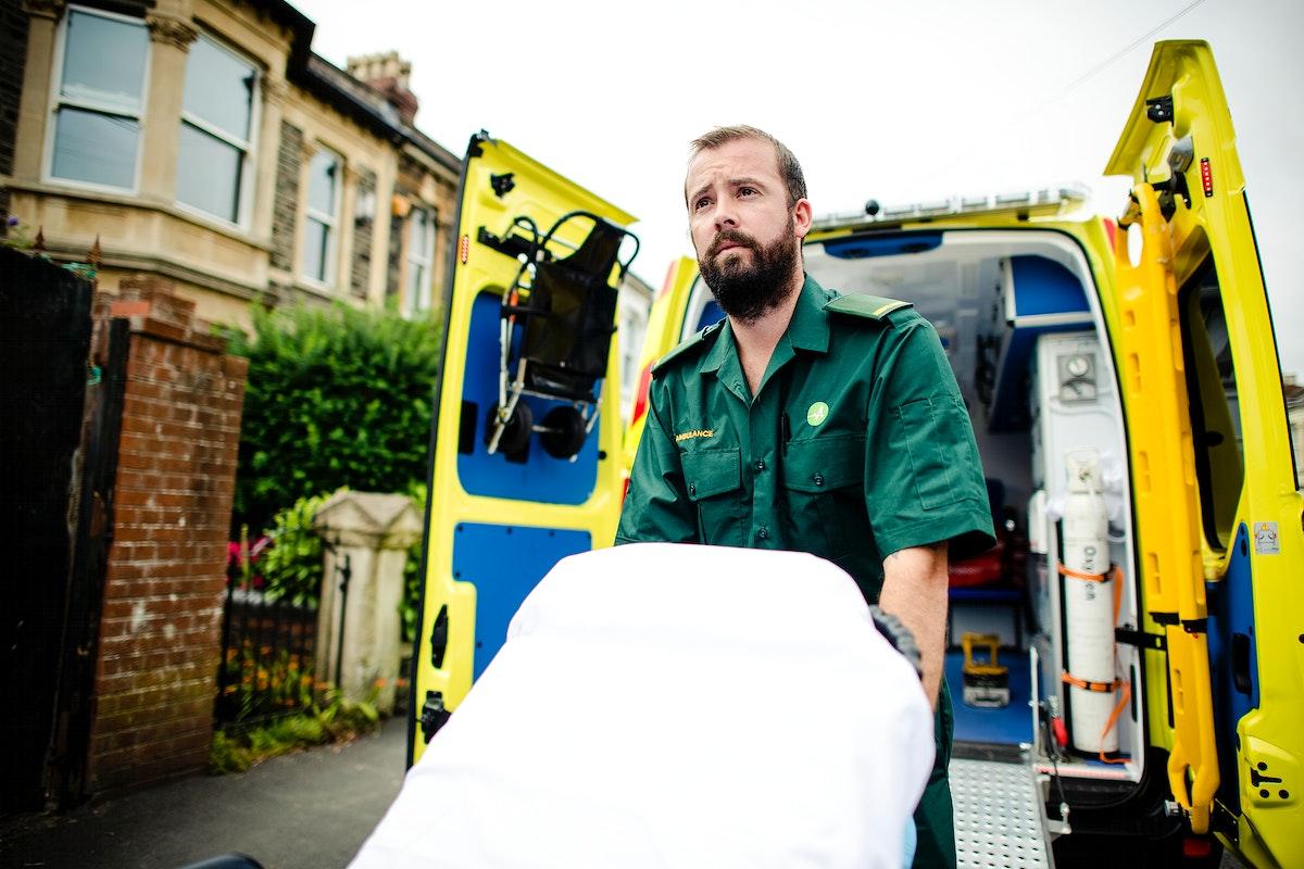Male paramedic moving the ambulance stretcher