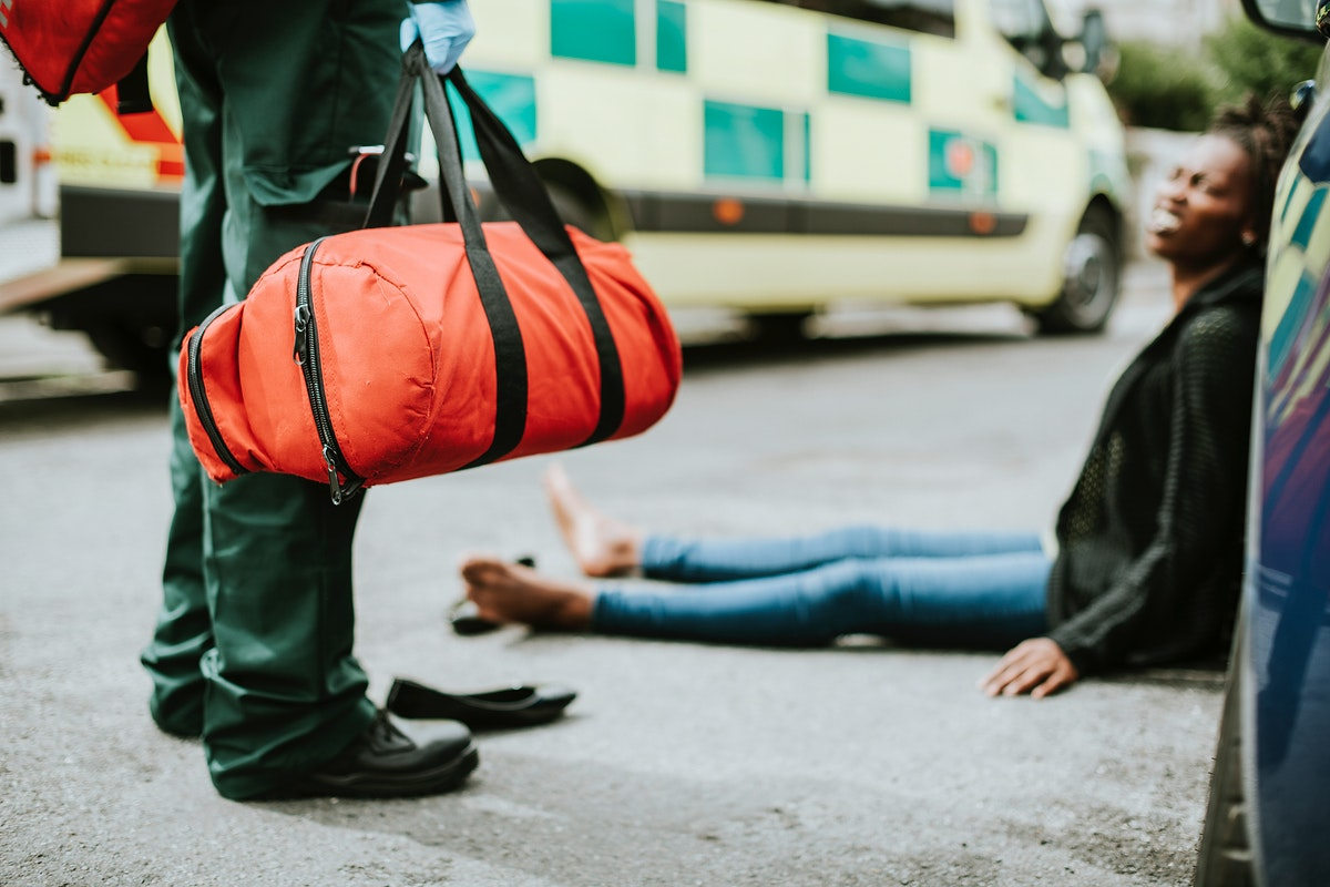 Male paramedic responding to a car accident