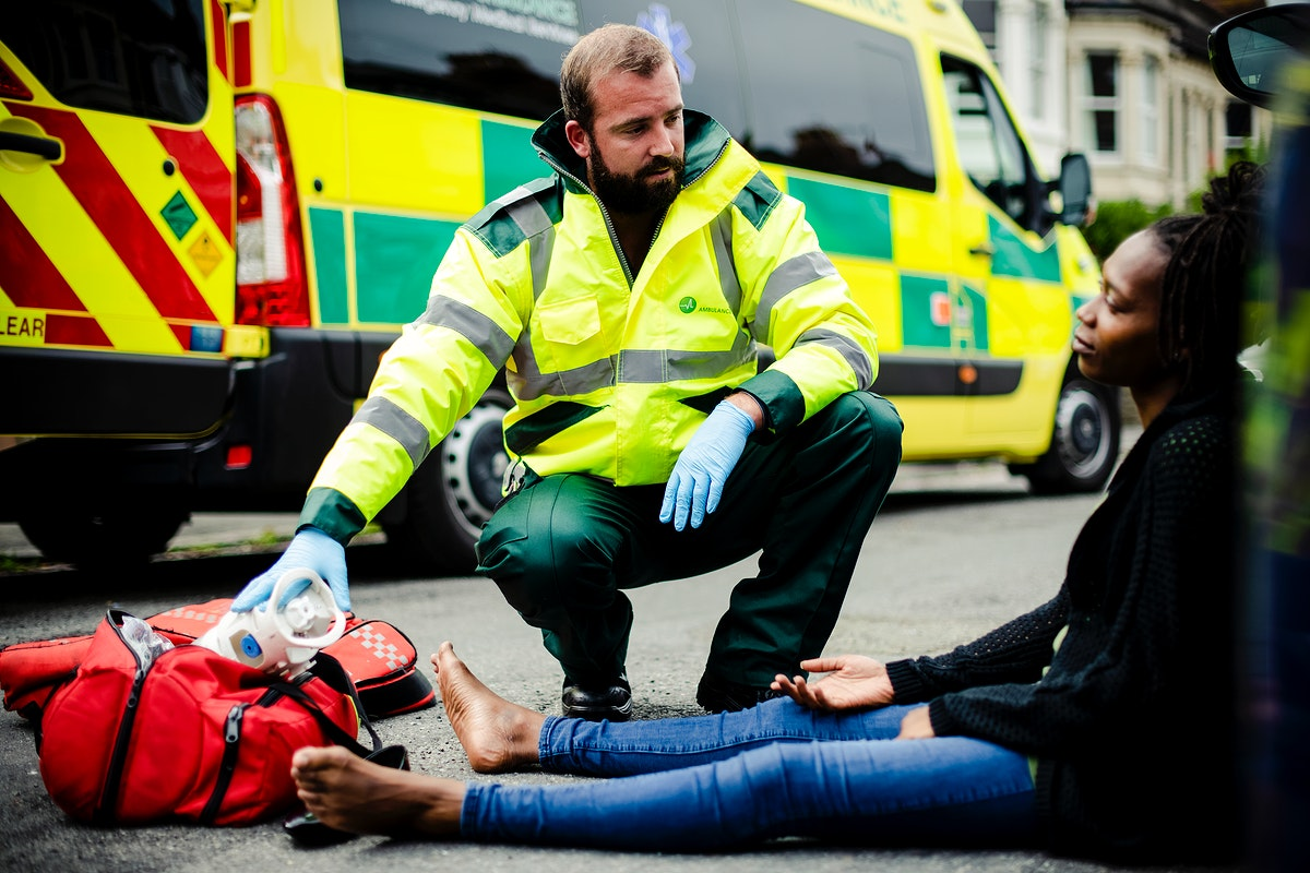 Male paramedic checking on an injured woman on a road