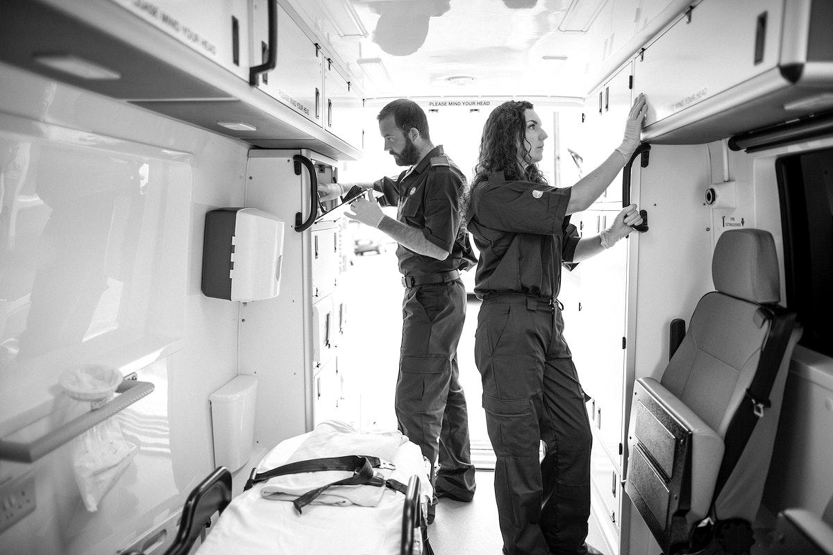 Paramedic team checking equipment in an ambulance