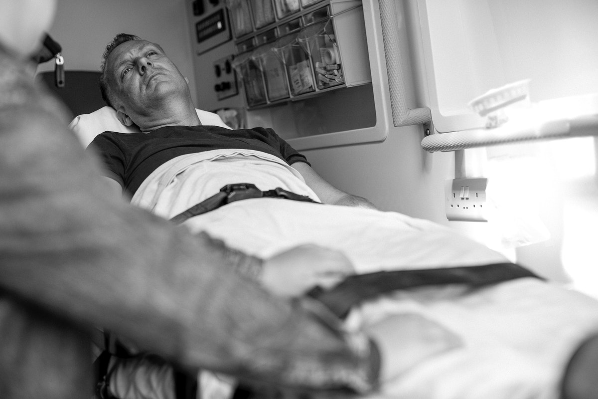 Worried patient lying on a stretcher in an ambulance