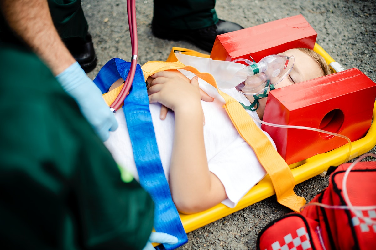 Paramedic team rescuing a young critical patient