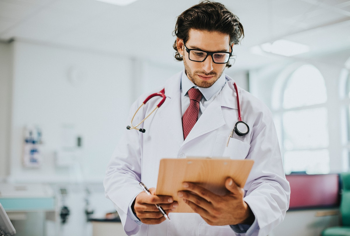 Male physician reading a medical report