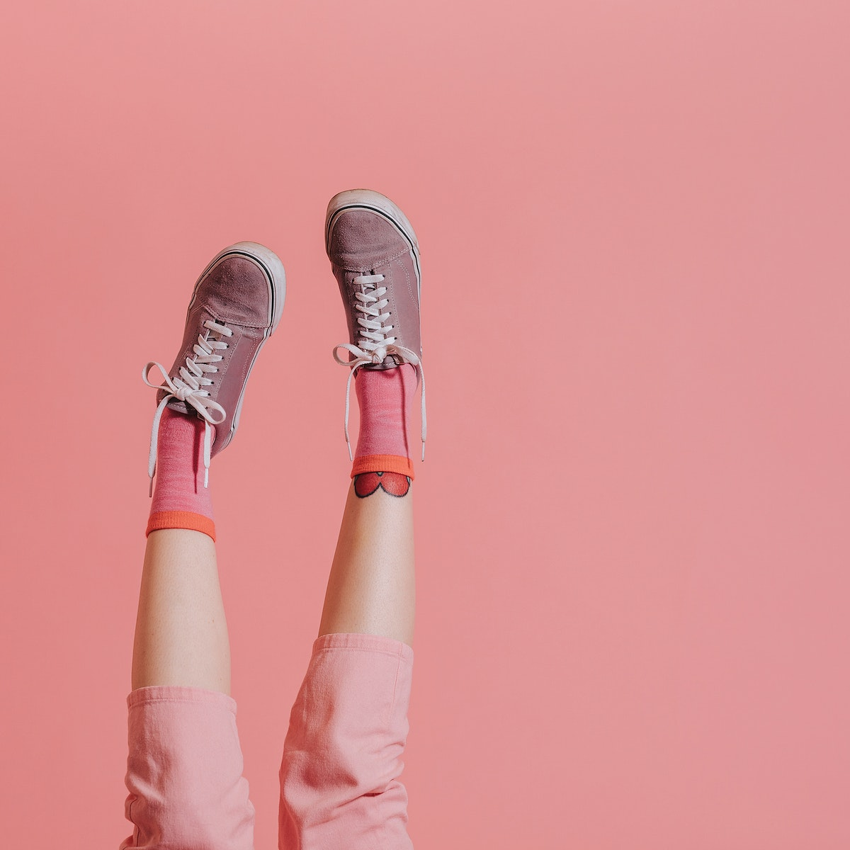 Woman legs in pink pants up in the air