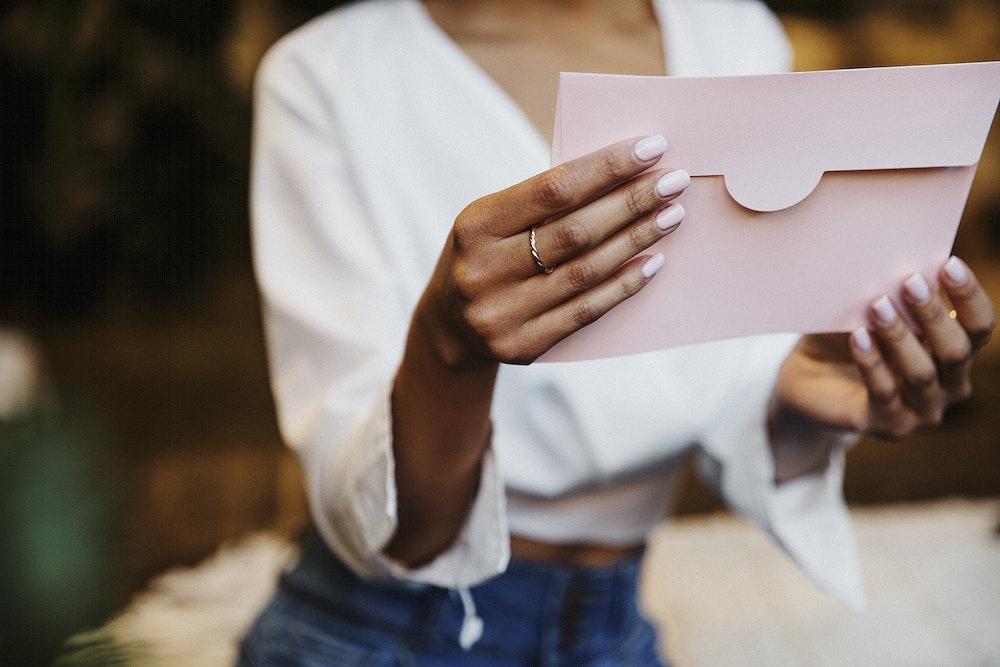 Woman reading a wedding invitation card