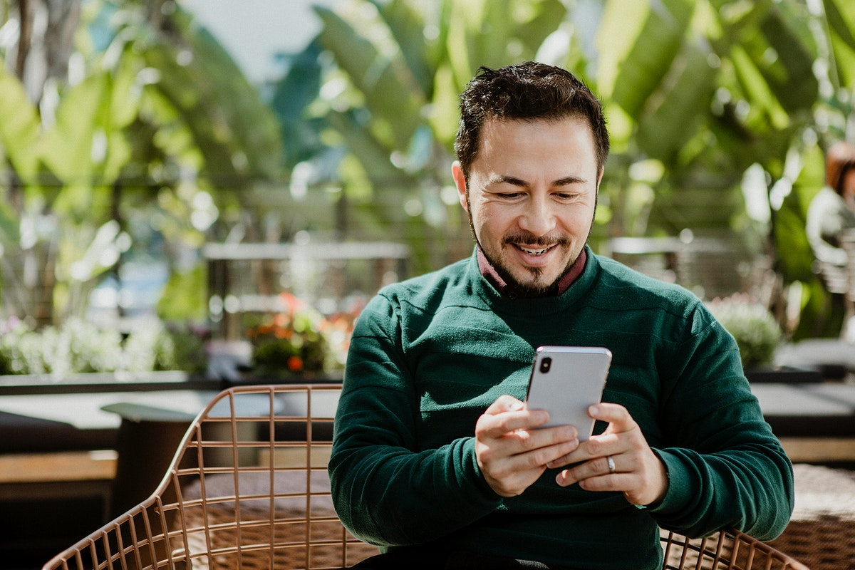Happy man using a smartphone in a cafe