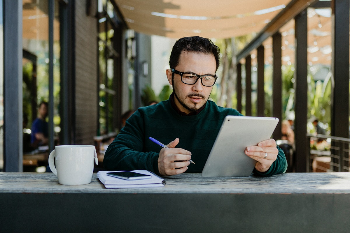Man making notes while using a tablet