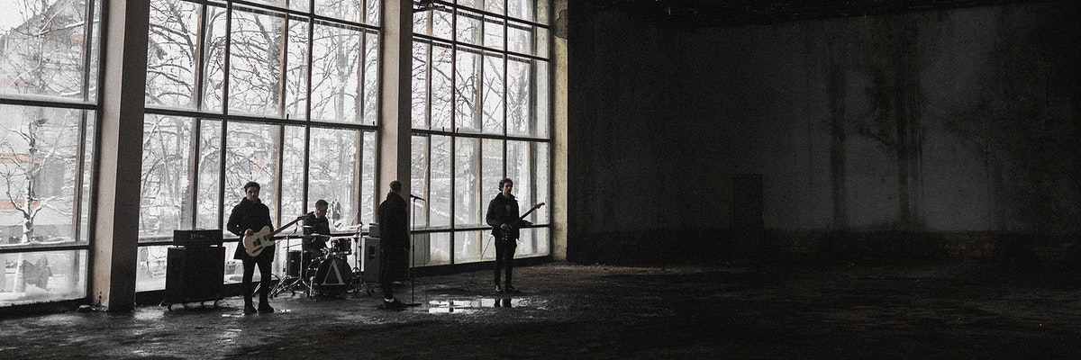 Rock band rehearsing in an abandoned building social banner