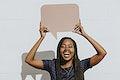 Cheerful black woman showing a blank speech bubble