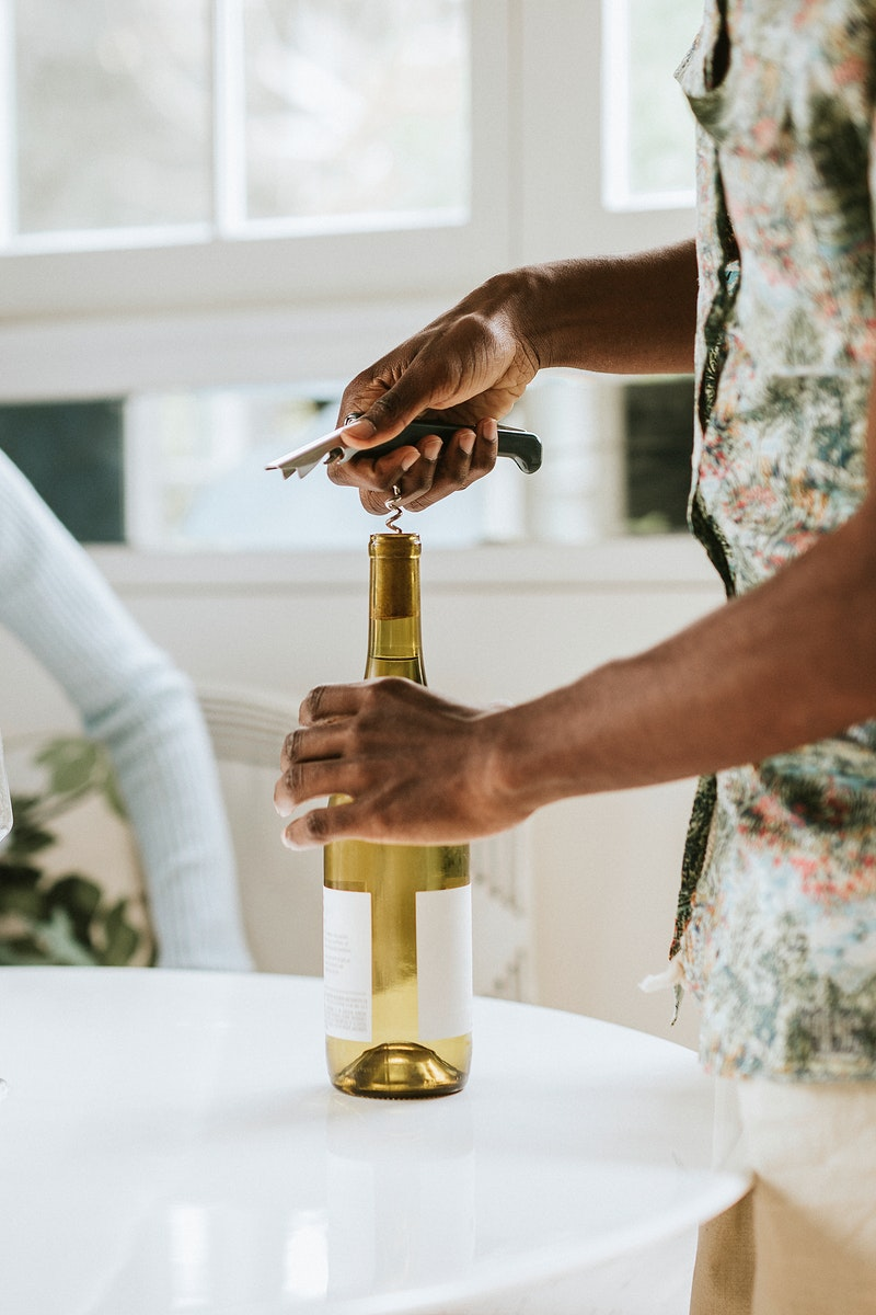 Black man uncorking a white wine bottle