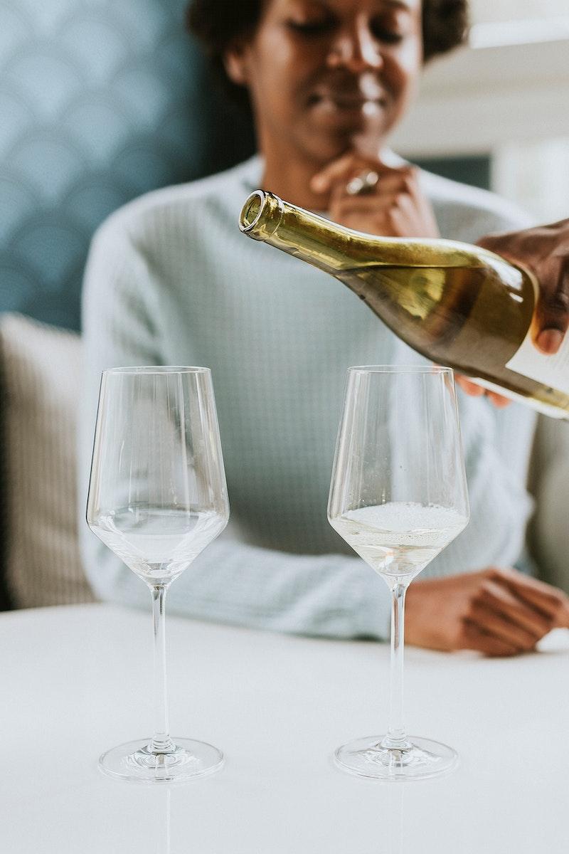 Black man pouring white wine into a glass