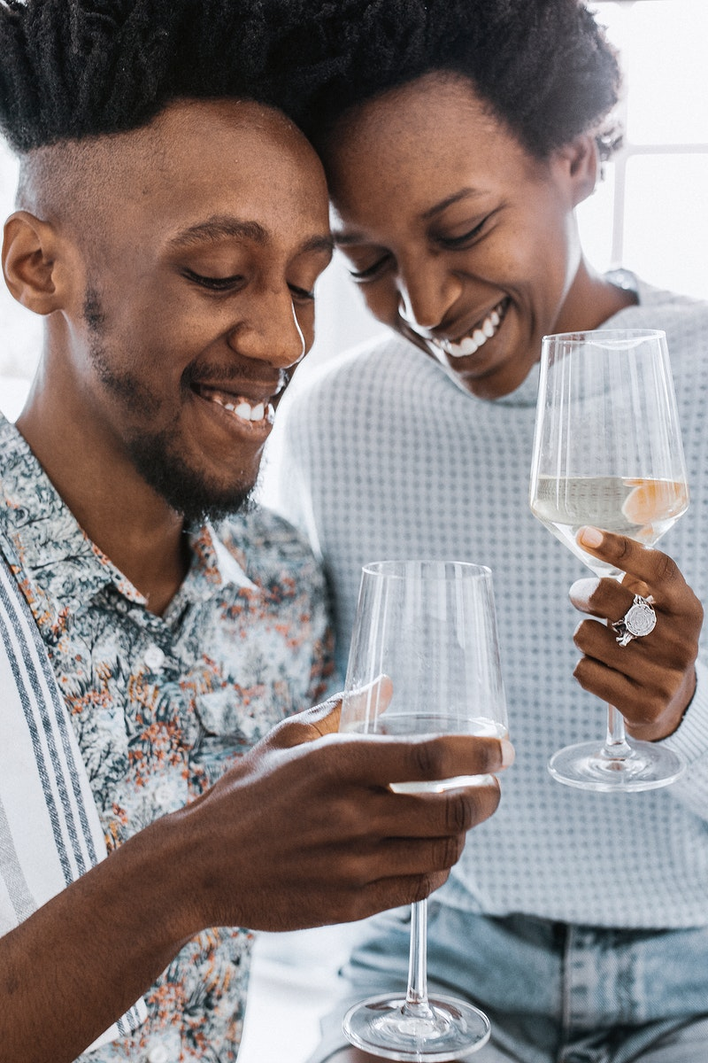 Happy couple enjoying a glass of wine in the kitchen