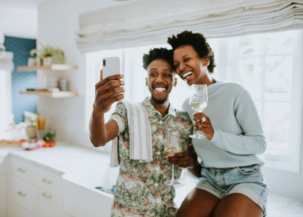 Happy couple taking a selfie in the kitchen