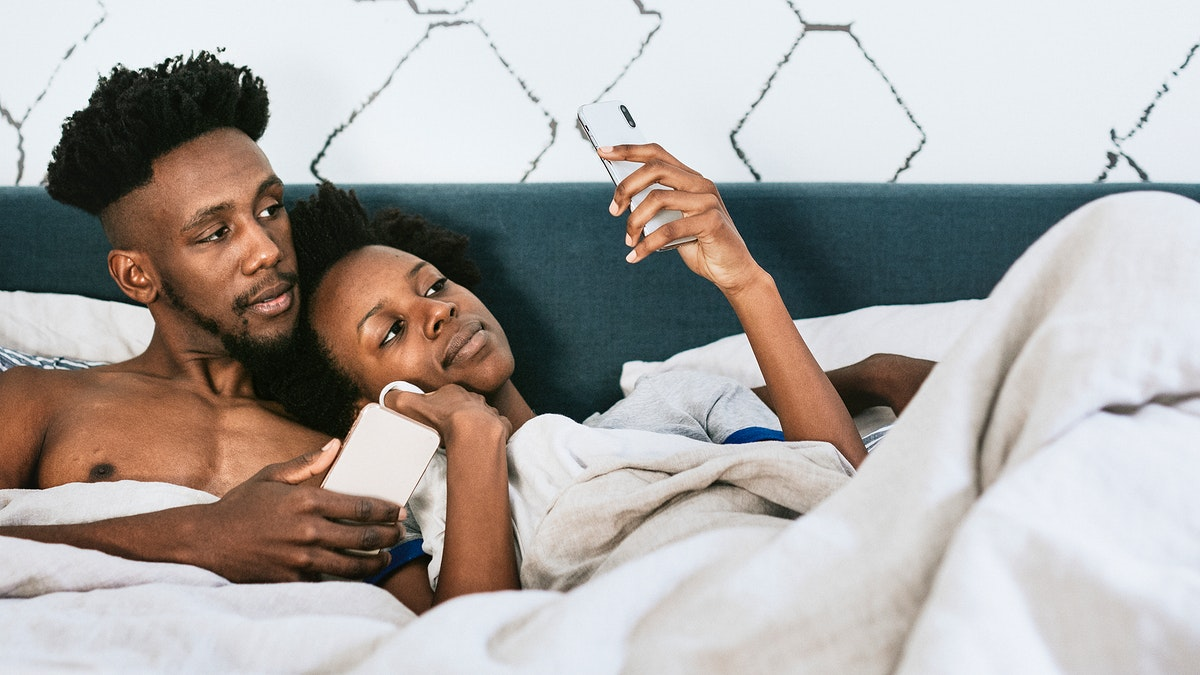Black couple watching a video on a phone in bed