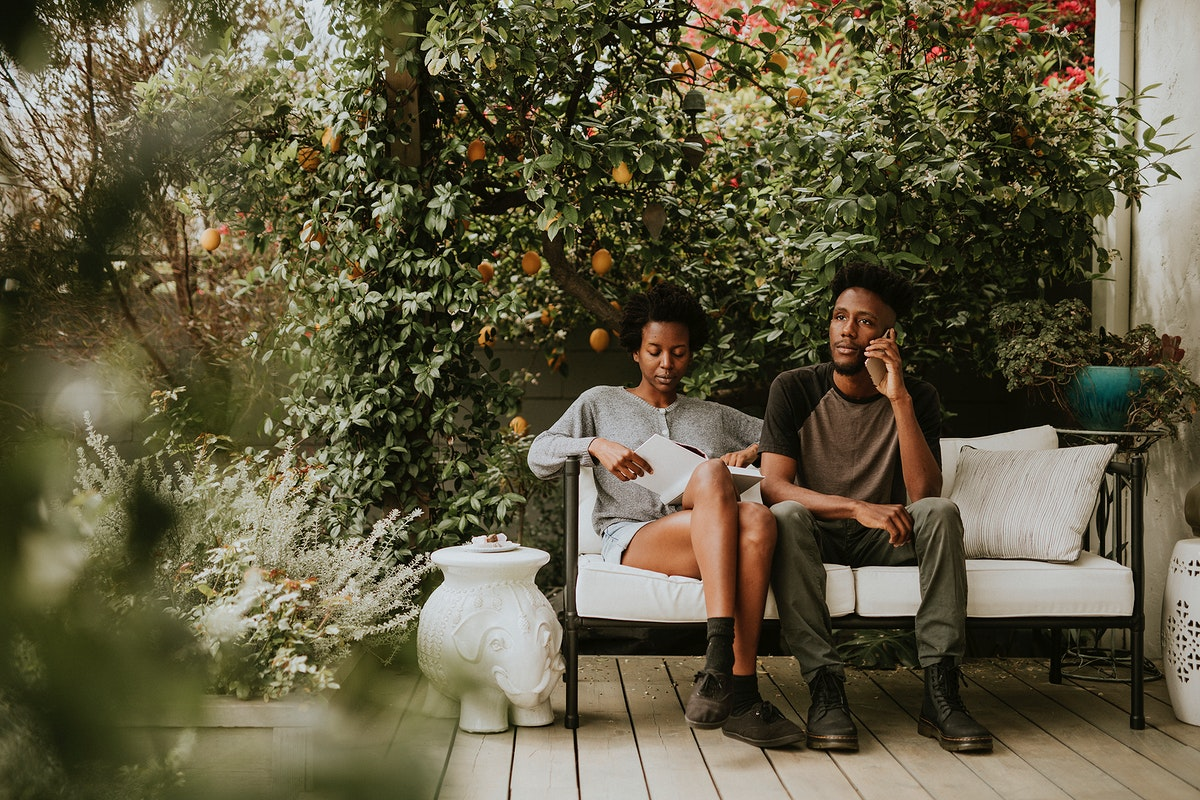 Black couple hanging in the garden with a book and a smartphone