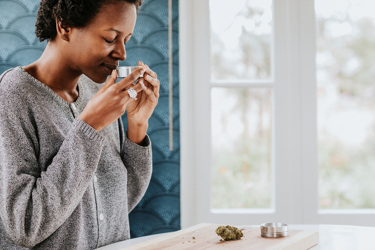 African woman smelling a weed
