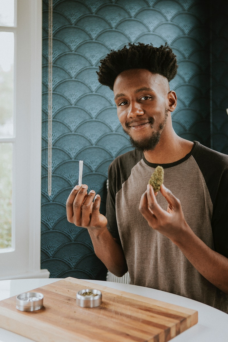 A man holding a joint and weed  in hand