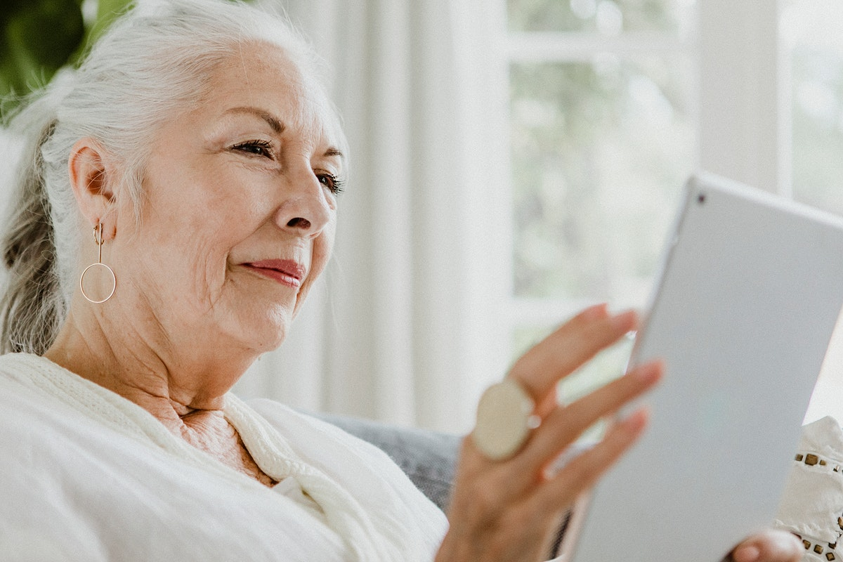 Elderly woman using a tablet on a couch