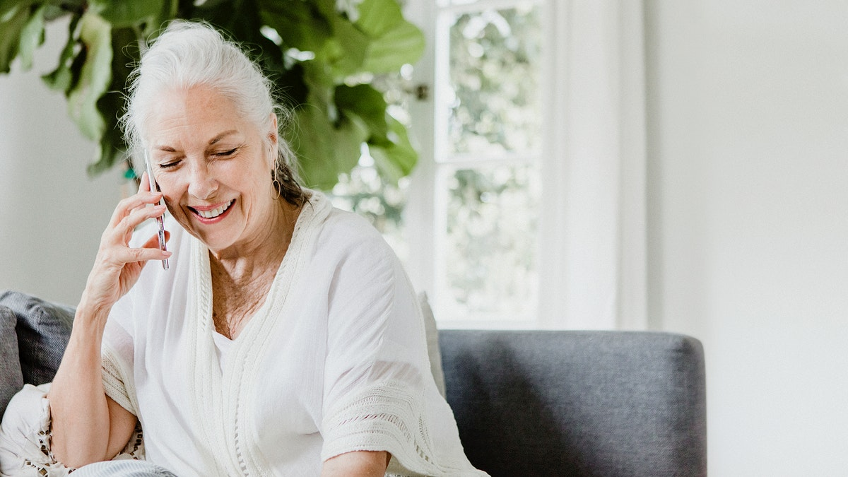 Cheerful elderly woman talking on a phone on a couch