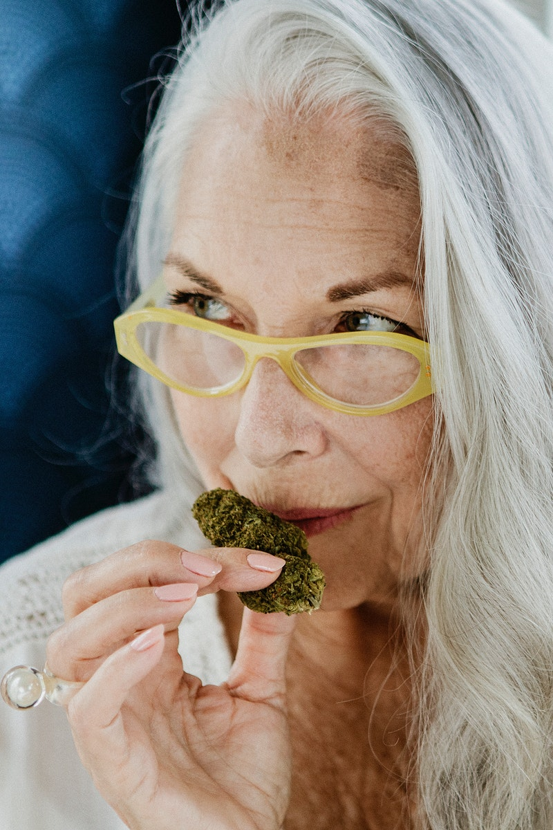 Senior woman smelling a weed