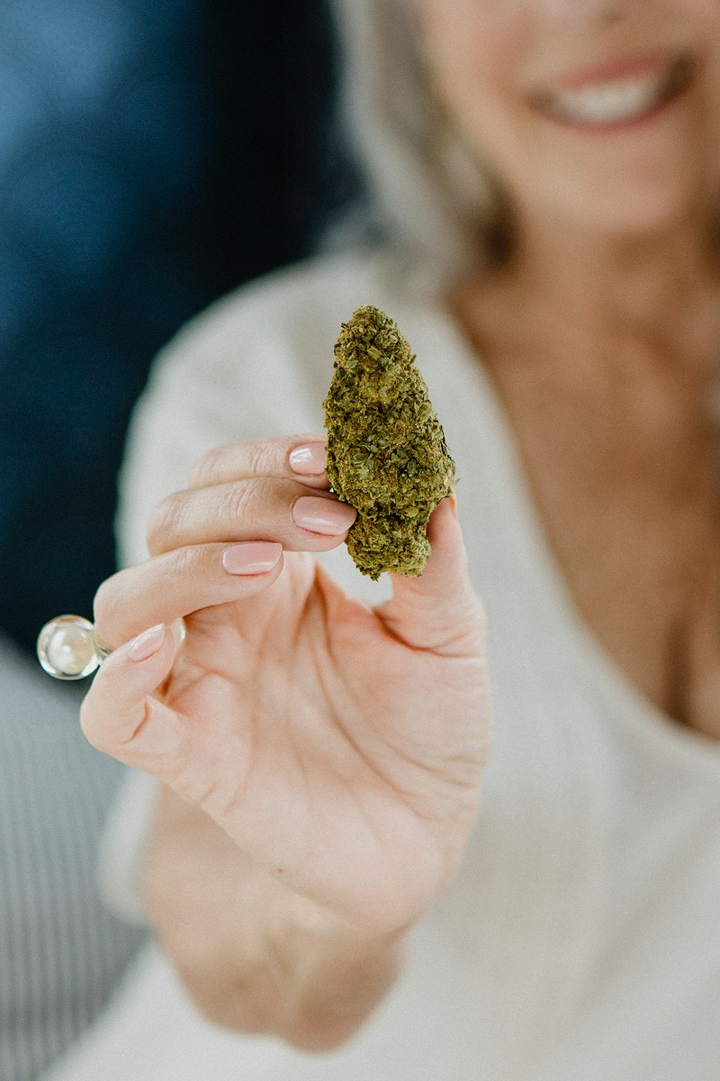 Hand holding a green weed