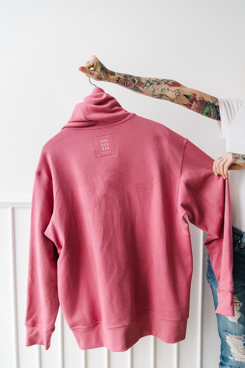 Tattooed woman holding a pink hoodie mockup