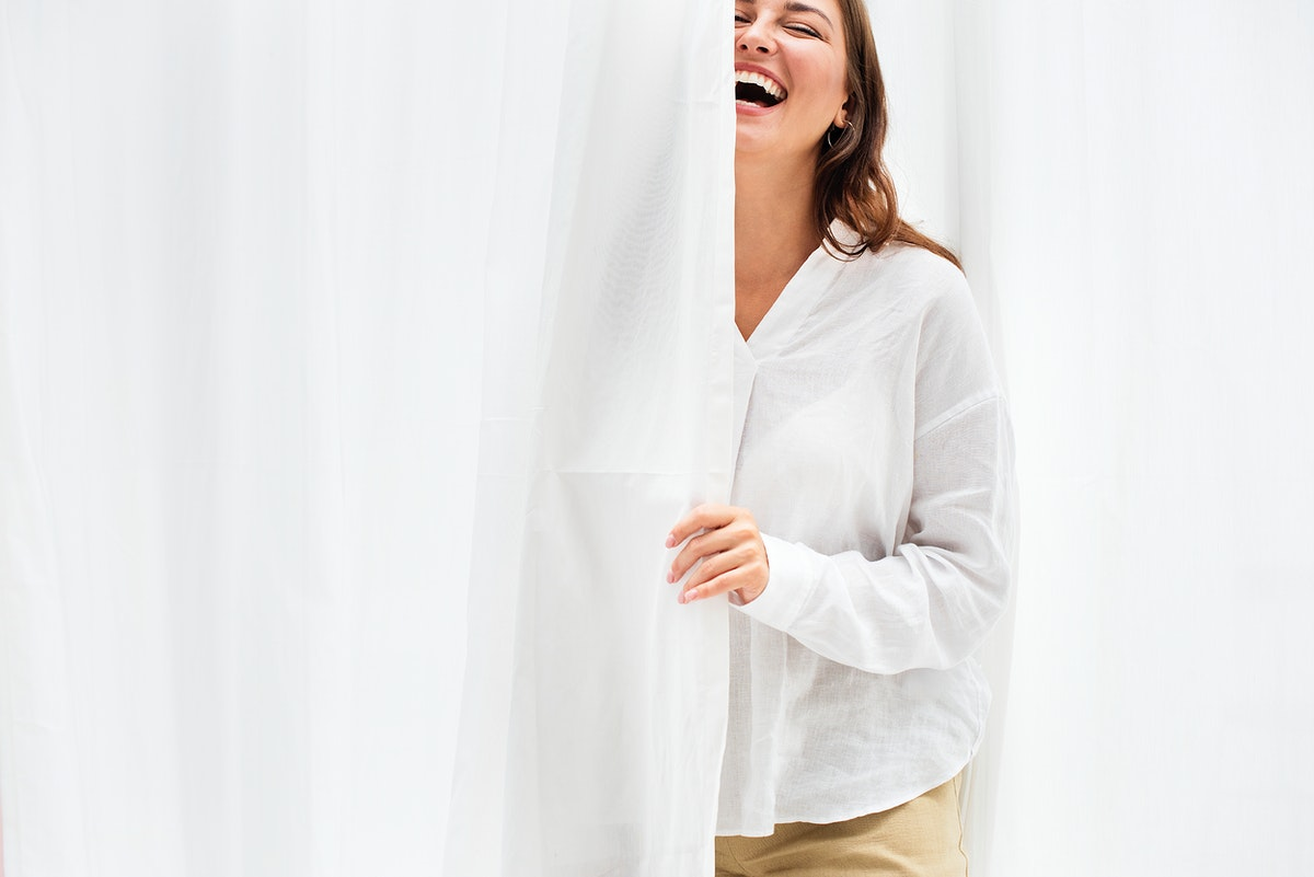 Smiling woman by the white curtain