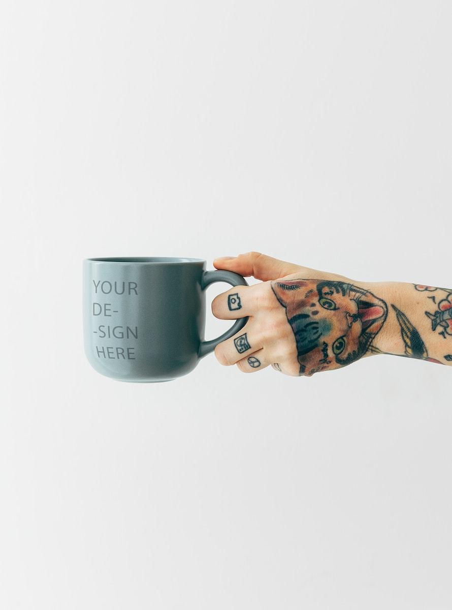 Tattooed hand holding a grayish blue coffee cup mockup