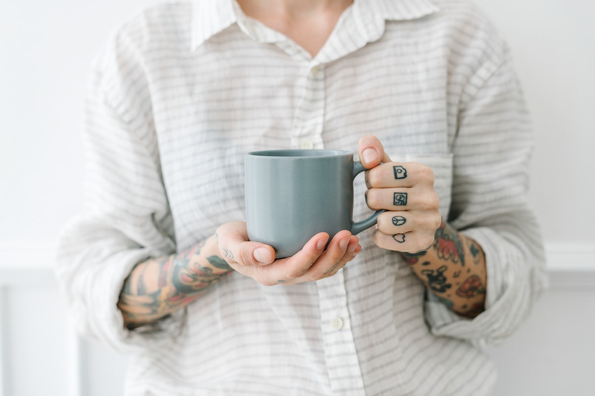 Tattooed woman with a cup of coffee