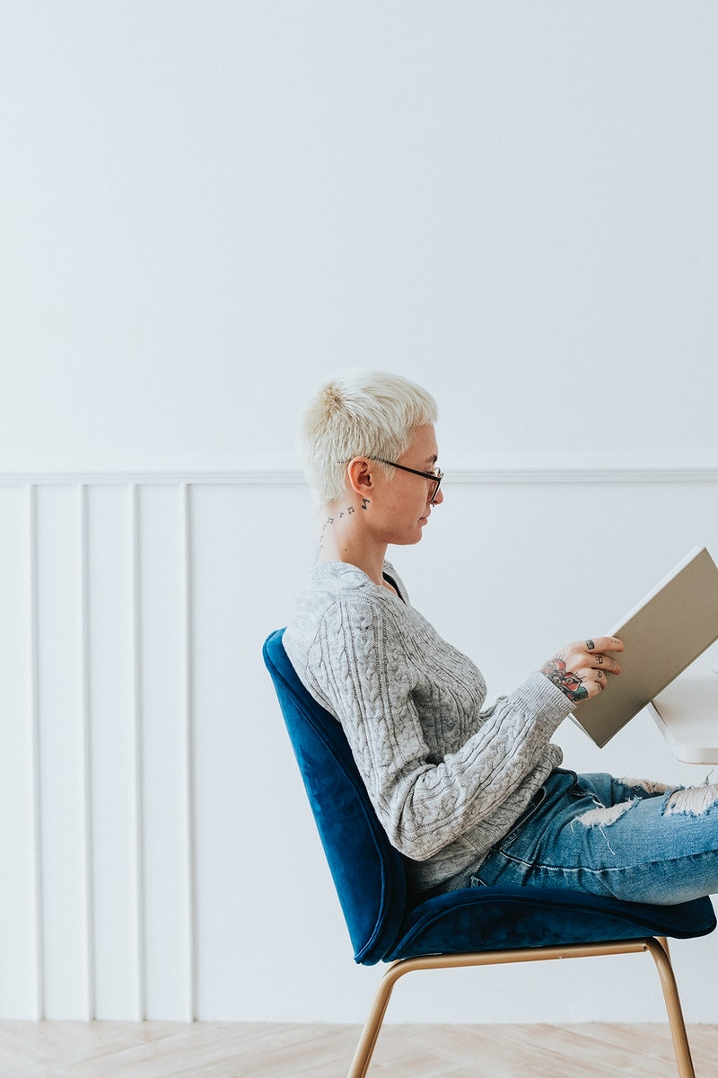 Woman sitting on a blue velvet chair reading a book