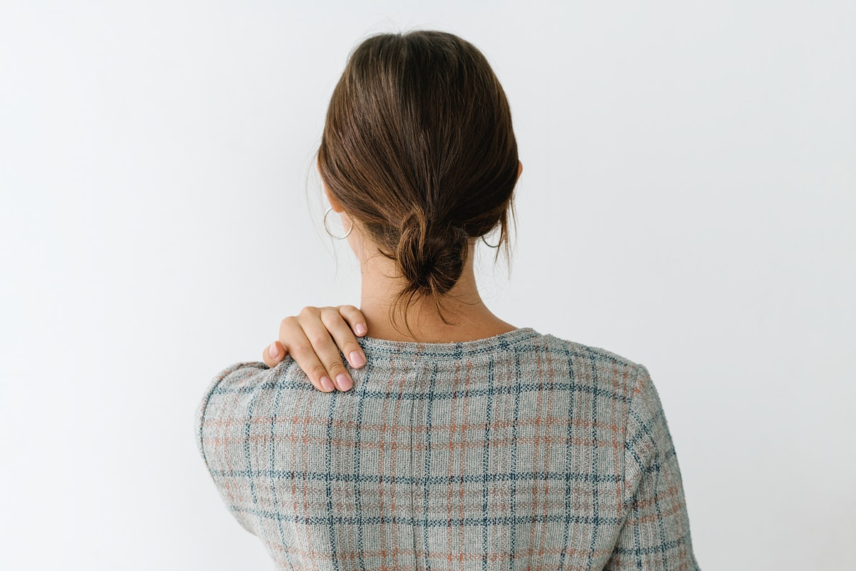 Rearview of a tired woman in a gray plaid dress