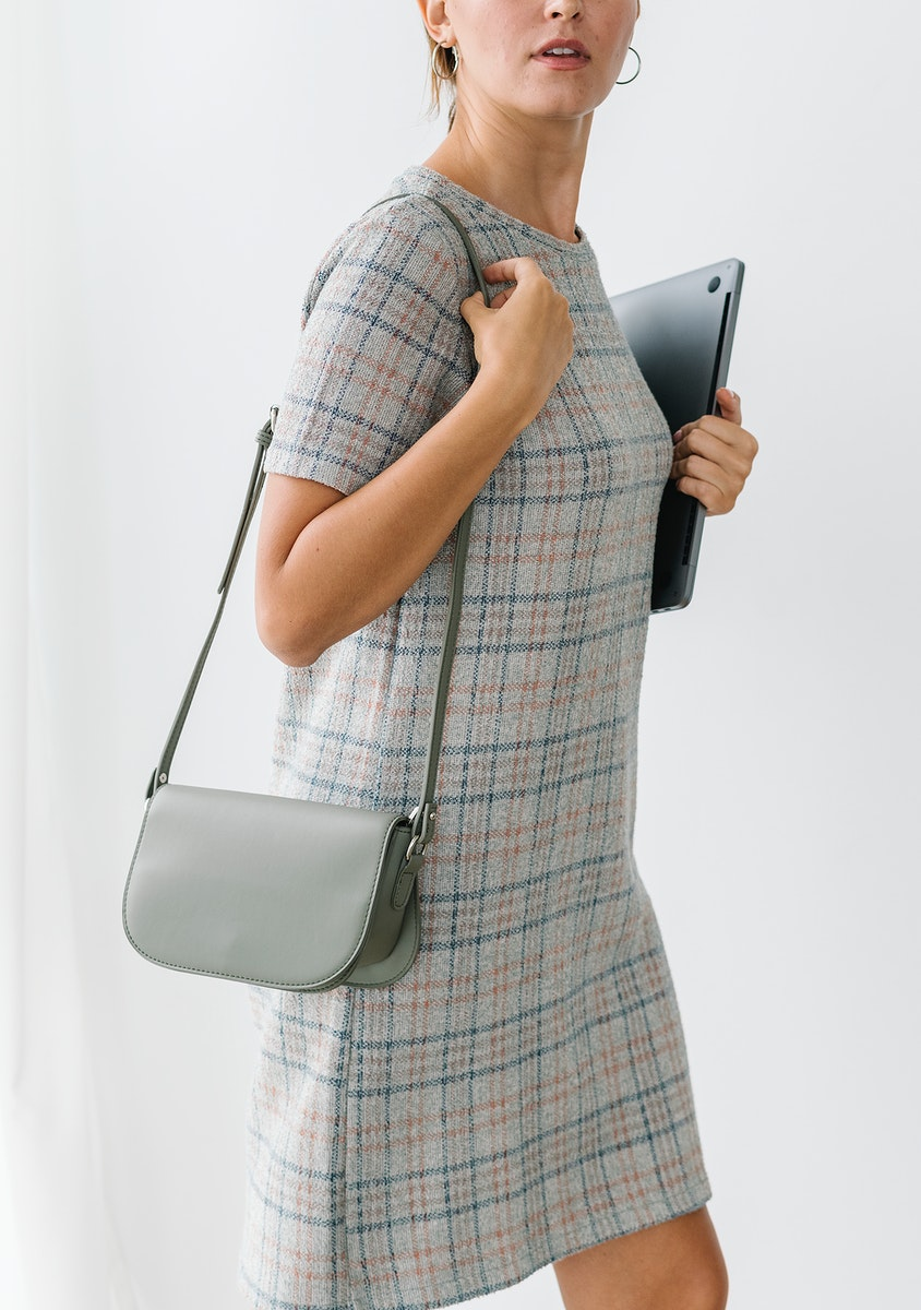 Woman in a gray plaid dress holding a laptop