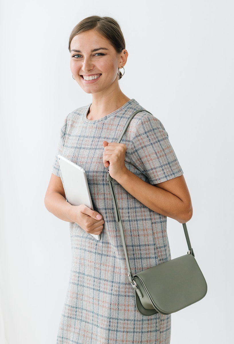Woman in a gray plaid dress holding a tablet