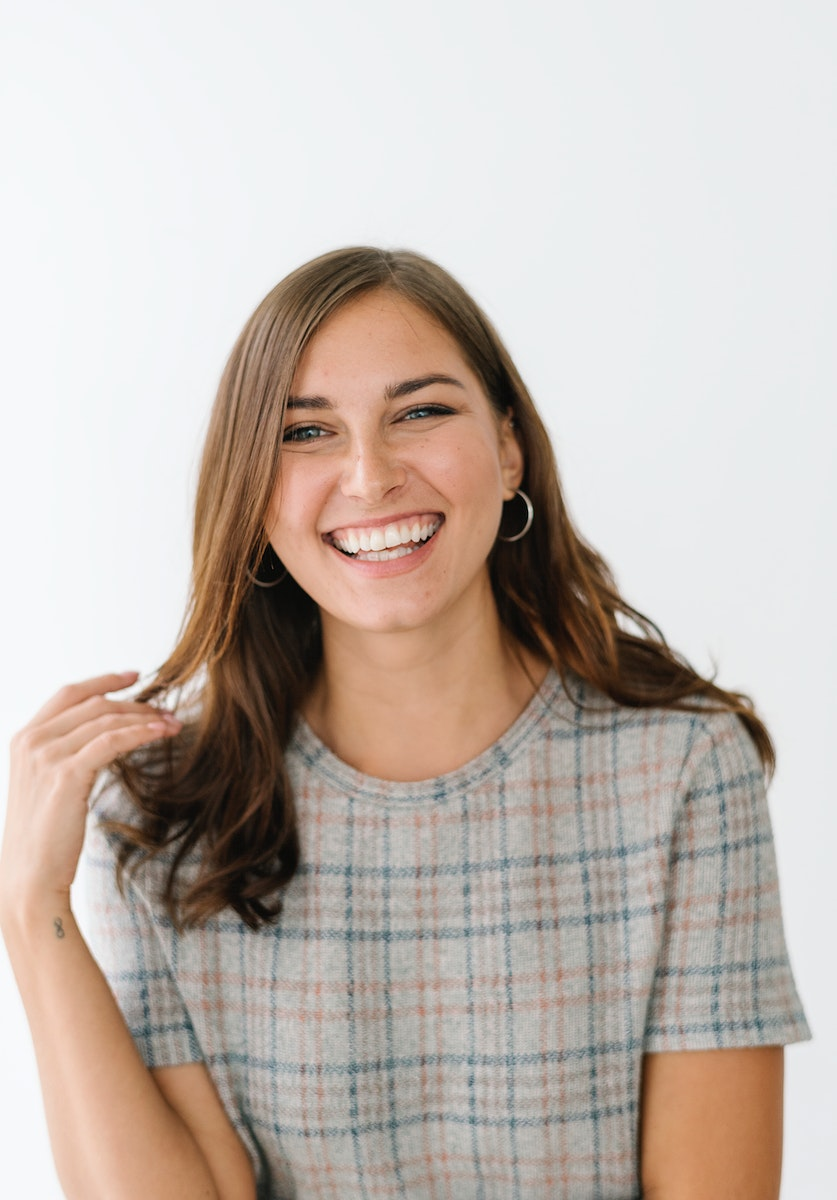 Smiling woman in a gray plaid dress
