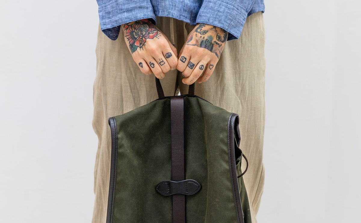 Tattooed hands holding a green bag