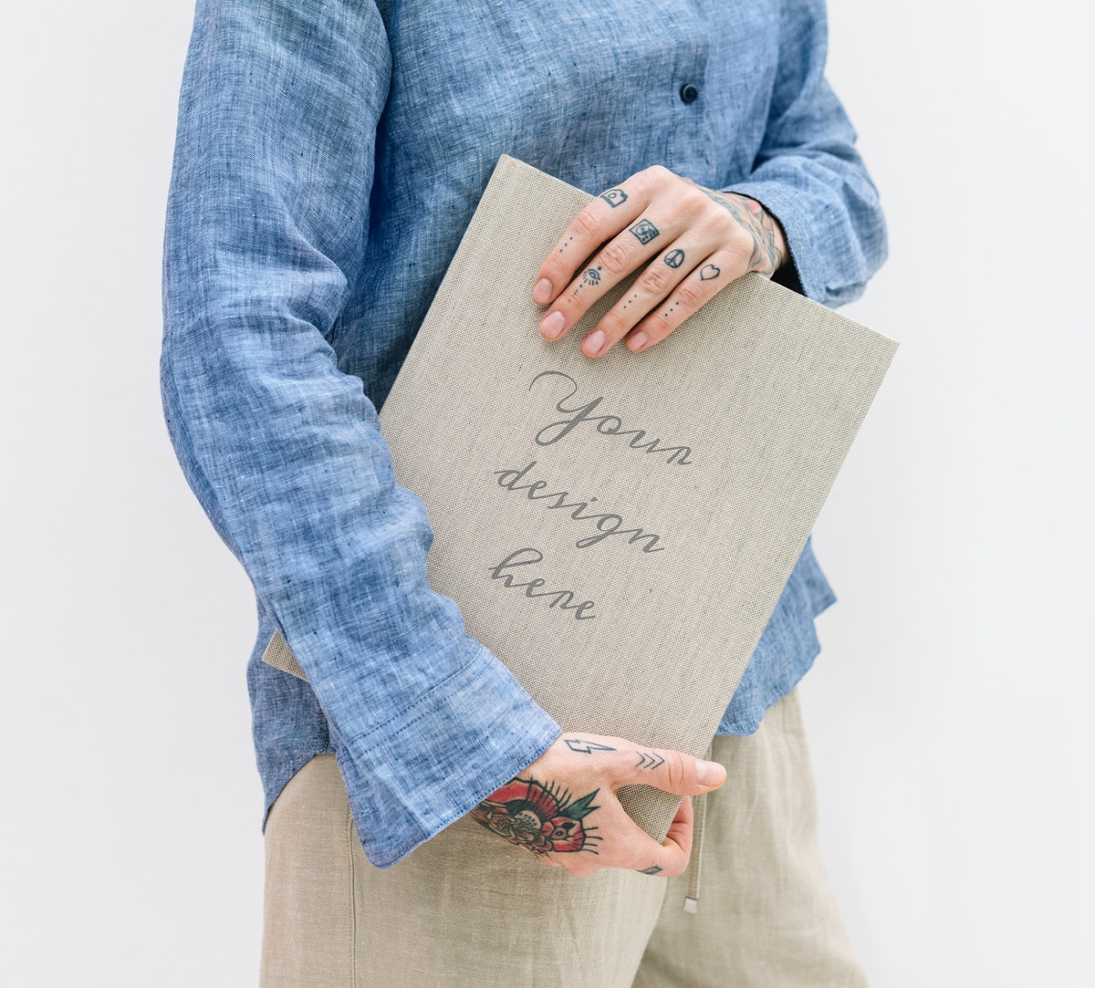 Tattooed woman in a blue linen shirt holding a book mockup