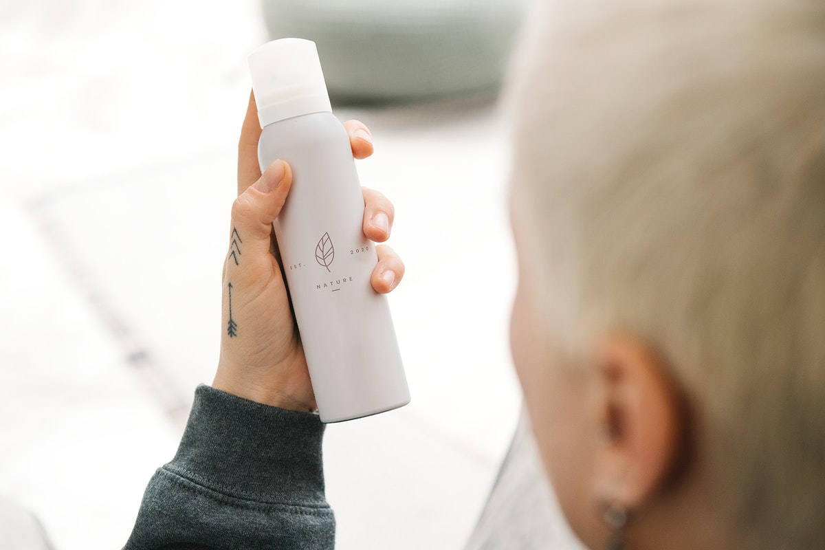Blond hair woman holding a white spray bottle mockup