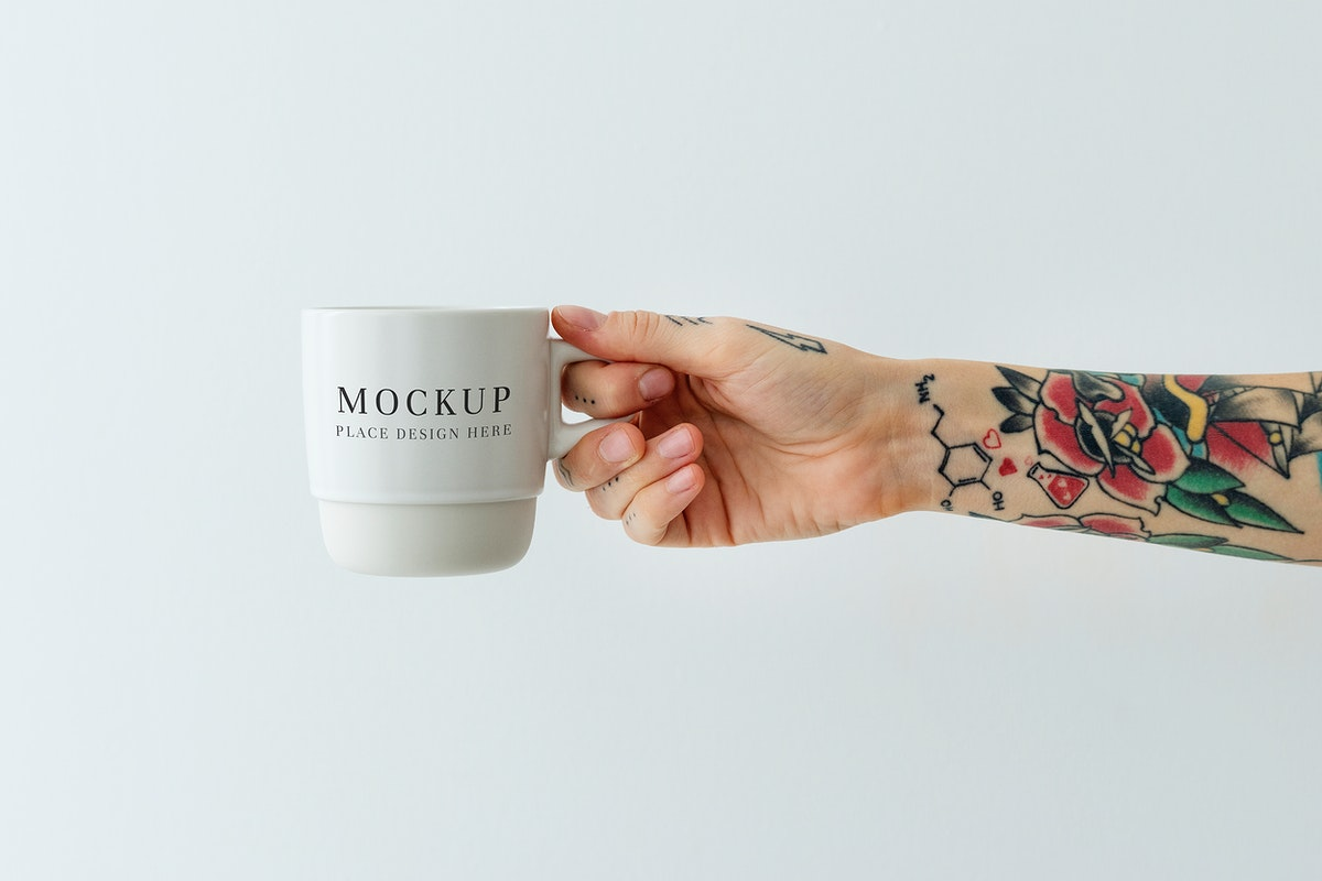 Tattooed hand holding a white coffee cup mockup